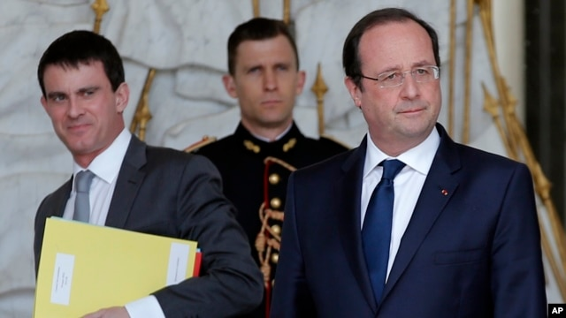 French Interior minister Manuel Valls, left, and  President Francois Hollande, after the weekly cabinet meeting in Paris, March 19, 2014.