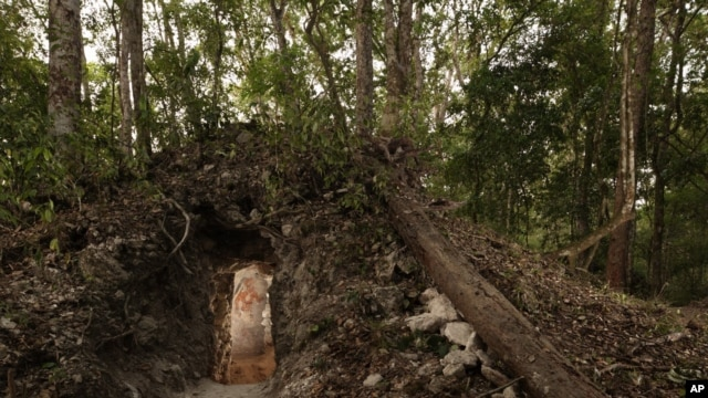 The painted figure of a man — possibly a scribe who once lived in the house built by the ancient Maya —  is illuminated through a doorway to the dwelling, in northeastern Guatemala. (Tyrone Turner © 2012 National Geographic)