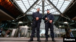 Belgian police officers stand guard at the entrance of the Justice Palace at the start of a trial against the Sharia4Belgium group, in Antwerp Sept. 29, 2014.