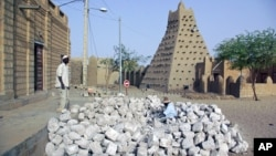 In this May 1, 2012 photo, men work alongside one of Timbuktu's historic mud mosques in Mali.