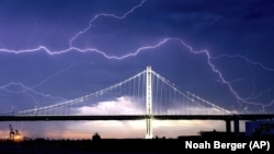 FILE - In this Aug. 16, 2020, file photo, lightning forks over the San Francisco-Oakland Bay Bridge as a storm passes over Oakland, Calif. Numerous lightning strikes led to brush fires throughout the area.