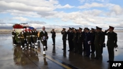 A picture released and taken on November 30, 2015 by Turkish army press office shows Turkish soldiers walking by officials of Russian army as they carry the coffin of Russian pilot Lt. Col. Oleg Peshkov into a Russian Air Force transport during a ceremony