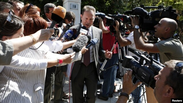 Greece's Finance Minister Yannis Stournaras is surrounded by the media as he leaves the Prime Minister's office in Athens, September 10, 2012.