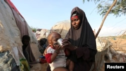 FILE - Rukia Nur feeds her child outside her makeshift dwelling after fleeing famine in the Marka Lower Shebbele regions to the capital Mogadishu.