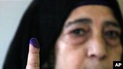 ແມ່ຍິງອີຈິບຄົນນຶ່ງສະແດງໃຫ້ເຫັນນໍ້າມຶກຕິດນີ້ວຊີ້ຂອງລາວ ຫລັງຈາກນາງປ່ອນບັດເລືອກຕັ້ງຮອບສຸດທ້າຍແລ້ວໃນແຂວງ Qalyobeia, ອີຈິບ. ວັນທີ 3 ມັງກອນ 2012.