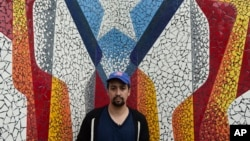 Actor and composer of Puerto Rican descent Lin Manuel Miranda stands in front of a mural in La Placita de Güisin, in Vega Alta, Puerto Rico, Nov. 7, 2017.