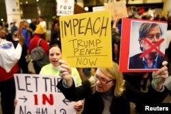 Seorang wanita memegang poster, mendorong pemakzulan Trump dan Pence selama protes larangan perjalanan Donald Trump dari negara-negara mayoritas muslim di Bandara Internasional Los Angeles (Foto: Reuters)