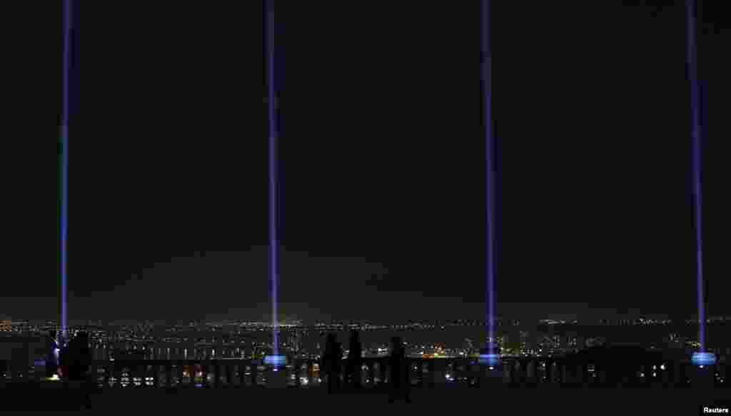 Cahaya berwarna biru ditembakkan untuk menandai peringatan 25 tahun penembakan 14 perempuan sampai tewas oleh seorang pria bersenjata di Ecole Polytechnique, Montreal, Quebec, 6 Desember 2014.