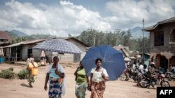 Des femmes déplacées par l'éruption du volcan Nyiragongo marchent dans la rue à Minova, à 50 kilomètres au sud de Goma, la capitale provinciale du Nord-Kivu, le 2 juin 2021.