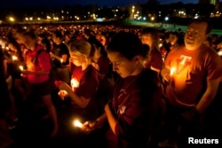 FILE - Members of the community reflect as they hold candles during a commemoration and candlelight vigil on the campus of Virginia Tech in Blacksburg, Virginia, April 16, 2012, five years after a mentally ill student gunned down 32 people at the university.
