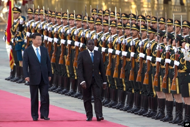 Chinese President Xi Jinping, left, walks with Zimbabwe's President Robert Mugabe during a welcome ceremony outside the Great Hall of the People in Beijing, China, Aug. 25, 2014.