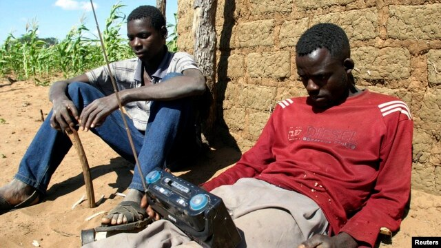 FILE - Zimbabweans listen to a radio for an announcement of election results in Umguza, Apr. 1, 2008.