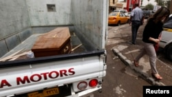 A woman walks past a truck carrying a wooden coffin of a man killed during an attack on liquor stores in Baghdad, Iraq, May 15, 2013.