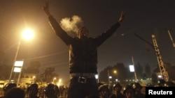 Người biểu tình chống ông Morsi giơ dấu hiệu chiến thắng phía trước lực lượng an ninh đang chặn con đường dẫn đến dinh tổng thống ở Cairo, ngày 6/12/2012.