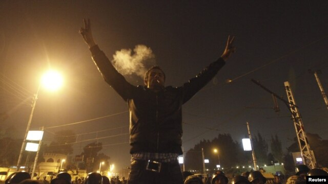 An anti-Morsi protester smokes a cigarette and and gestures in front of members of the Republican Guard blocking a road to the presidential palace in Cairo, Egypt, December 6, 2012.