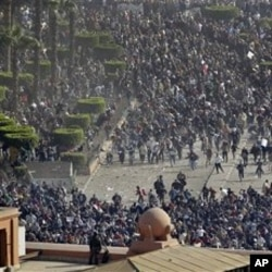 Pro-government demonstrators, below, clash with anti-government demonstrators, above, as an Egyptian Army soldier on the rooftop of the Egyptian Museum observes the scene in Tahrir square, in Cairo, February 02, 2011.