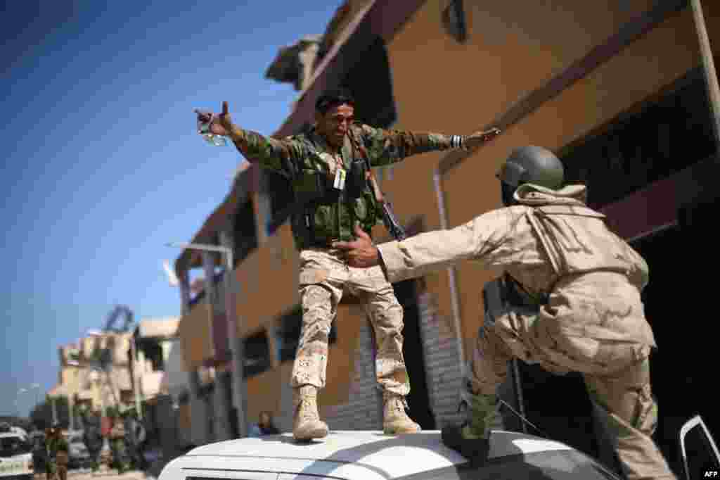 October 20: Revolutionary fighters celebrate the capture of Sirte, Libya. Moammar Gadhafi was killed Thursday when revolutionary forces overwhelmed his hometown, Sirte, the last major bastion of resistance two months after the regime fell. (AP Photo/Manu