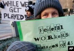 """Esther Anastasia, una mujer en Boston, Massachusetts, sostiene un cartel que dice """"Trabajadores Federales rehenes de 45"""" en referencia al presidente Trump, durante una protesta el viernes 11 de enero de 2019. Los trabajadores protestaron junto con el senador demócrata Ed Markey y otros partidarios para instar al presidente Trump a reabrir el gobierno."""