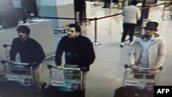 """A screengrab of airport CCTV footage released by Belgian federal police shows suspects in the attacks at Brussels Airport, in Zaventem, March 22, 2016. Police is seeking help in identifying the """"man in the hat"""" on the right."""