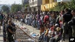 Polisi menjaga jalur kereta sebelum sebuah kereta yang membawa migran ke Serbia memasuki stasiun kereta di kota selatan Makedonia, Gevgelija, 23 Agustus 2015.
