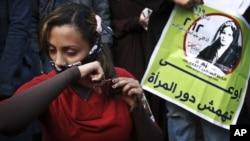 """Egipćanka seče kosu u znak protesta zbog novog ustava, na demonstracijama na trgu Tahrir, 25. decembra 2012. Na plakatu pored nje piše: """"ne marginalizovati položaj žena."""""""