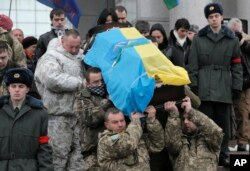 Ukrainian soldiers carry a coffin bearing the body of a fellow serviceman who was killed in fighting with pro-Russia rebels in eastern Ukraine, during his funeral in Kyiv Jan. 20, 2015.