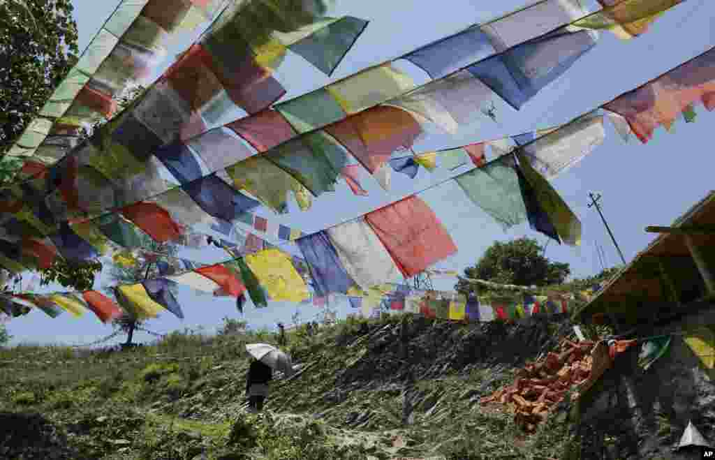 A Buddhist walks under prayer flags after paying her respects to those who died in the recent earthquake, at the Nedyon Unphong Thapchyo Monastery in Bidur, Nuwakot District, Nepal, May 4, 2015.