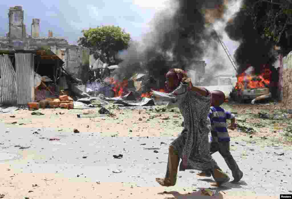 A Somali girl and her brother run to safety near the scene of a blast in Mogadishu, April 14, 2013.