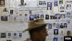 """Seorang melewati sebuah poster yang menunjukkan foto-foto """"warga Libya yang hilang"""" di sebuah rumah sakit di Benghazi (17/4)."""