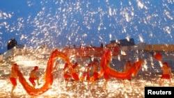 2013年2月10日在北京的一处游乐园庆祝农历新年的火龙舞表演中,火龙队员在铁水花与干花的施放中舞着火龙
