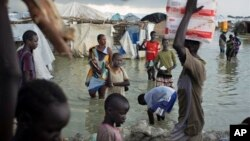 FILE - Displaced South Sudanese walk through flood waters to move around a makeshift camp.