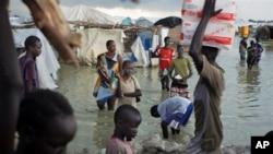 ARCHIVES - Des déplacé Sud-Soudanais traversent les eaux d'innondation pour vendre leurs produits agricoles près 'une base de la mission des Nations unies à Bentiu, Soudan du Sud, le 22 septenbre 2014.