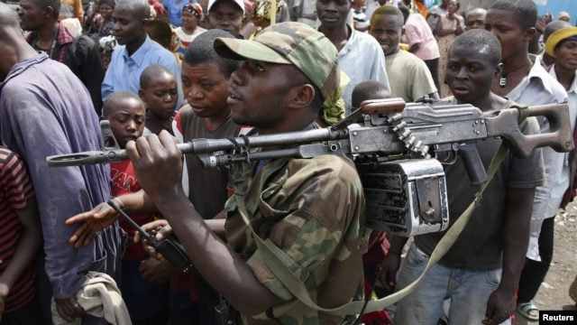 A M-23 rebel fighter walks with his rifle as they withdraw from Goma, December 1, 2012.