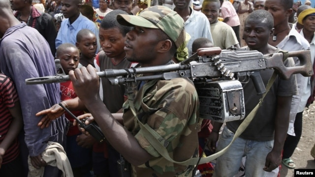 A M-23 rebel fighter walks with his rifle as the group withdraws from the eastern Congolese city of Goma, December 1, 2012.