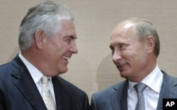 FILE - Russian Prime Minister Vladimir Putin, right, and Rex Tillerson, ExxonMobil's chief executive smile during a signing ceremony in the Black Sea resort of Sochi, Russia, Aug. 30, 2011.