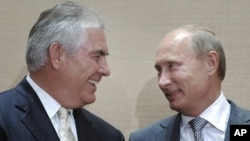 Russian Prime Minister Vladimir Putin, right, and Rex Tillerson, ExxonMobil's chief executive smile during a signing ceremony in the Black Sea resort of Sochi, Russia, Tuesday, Aug. 30, 2011