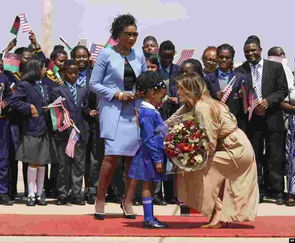 В Малаві Меланію Трамп зустріла перша леді Малаві Гертруда Масеко, а маленька дівчинка подарувала першій леді США квіти. Лумбадзі, Малаві, 4 жовтня 2018 року.