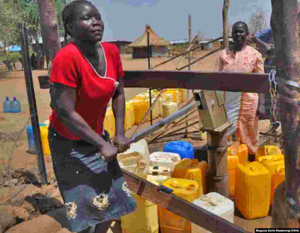 A young South Sudanese woman pumps water at a borehole in Gudere, near Juba, in South Sudan. The South Sudanese capital has grown from population of around 60,000 in 2005 to nearly 400,000 in 2011. The city's water resources have not been able to keep up.
