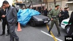 Pasukan keamanan Iran mengamankan lokasi ledakan bom di luar komplek sebuah universitas di Teheran (11/1). Ledakan ini menewaskan ilmuwan nuklir Iran dan melukai dua orang lainnya.
