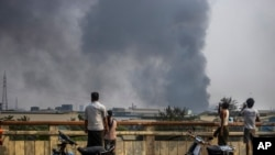 Black smoke billows from the industrial zone of Hlaing Thar Yar township in Yangon, Myanmar Sunday, March 14, 2021. Attacks on Chinese-run factories in Myanmar's biggest city drew demands Monday from Beijing for protection for their property and employees, while many in Myanmar e