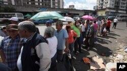 El gobierno del presidente Maduro asegura que las colas en los comercios son parte de una campaña en su contra.
