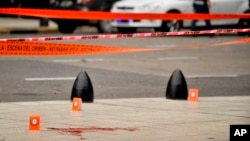 Evidence tent markers mark the crime scene where Argentine lawmaker Hector Olivares was seriously injured and another man was killed after they were shot at from a parked car near the Congress building in Buenos Aires, Argentina, May 9, 2019.