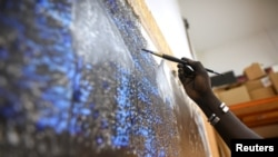 Senegalese artist Omar Ba paints on a canvas hanging from the wall of his studio in Bambilor, Senegal on March 12, 2021. REUTERS/ Cooper Inveen
