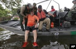 John Paul Klotz, 80, is pulled on a boat by U.S. Border Patrol Agents Steven Blackburn, left, Ramiro Rodriguez, top center, and Juan Flores during a search-and-rescue operation in a neighborhood inundated by floodwaters from Tropical Storm Harvey in Houston, Texas, Aug. 30, 2017.