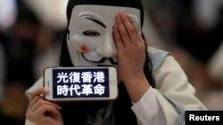 一名香港示威者在元朗地区一个商场的抗议活动中头戴面罩手举反送中运动口号。(2019年11月21日)