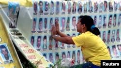 Seorang perempuan menangis di depan barisan foto orang hilang di kota Medellin, Kolombia. (Foto: Dok)