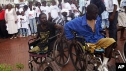 Two war victims seen in wheelchairs at the launch of Liberia's Truth and Reconciliation Commission in Monrovia, June 22, 2006. An accounting of atrocities committed during nearly a quarter-century was aimed at setting the stage for a long-term peace. (AP Photo/Pewee Flomoku)