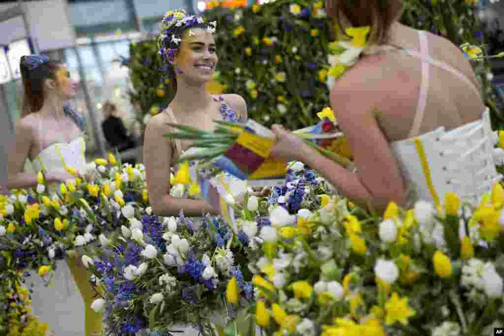 مدل ها با لباسهایی از گل در حال گفتگو با توریست ها در هلند