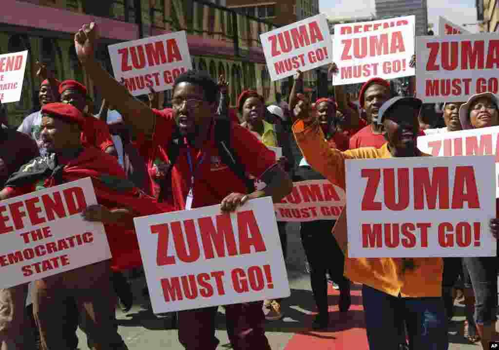 Manifestantes com cartazes exigindo saída de Zuma.
