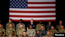 Military personnel watch as U.S. President Donald Trump announces his strategy for the war in Afghanistan during an address to the nation from Fort Myer, Virginia, Aug. 21, 2017.